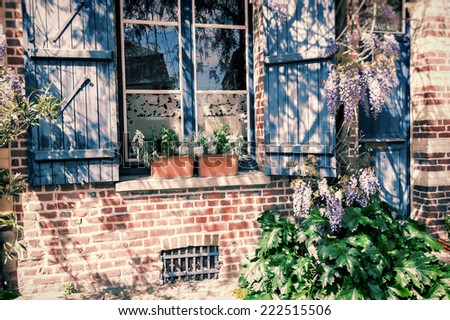 Old house window with blue shutters - stock photo