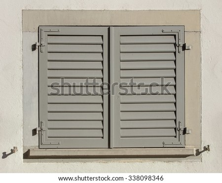 Old house window with closed wooden shutters.