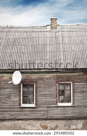 old house with a tiled roof with chimney and satellite dish near the window,dramatic blue sky background - stock photo