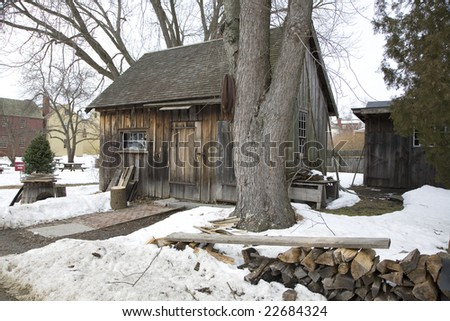 Old house with a wood chopping block and wood outside