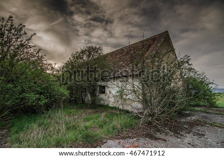 old house with dark rain clouds