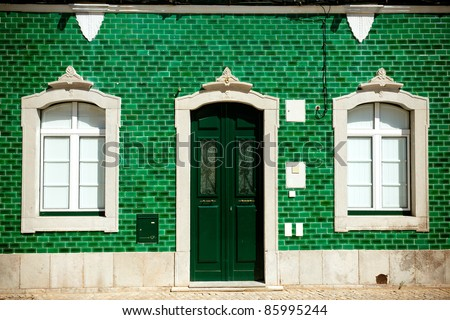 Old house with green tiles on facade - stock photo