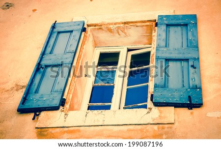 Old house with ocher stucco wall,  a window with blue wooden shutters in Roussillon ocher village. Provence Alpes Cote d'Azur, France. Aged photo. - stock photo
