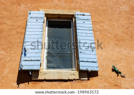 Old house with ocher stucco wall,  a window with blue wooden shutters, mosquito net and funny ceramic lizard attached to the wall in Roussillon ocher village. Provence Alpes Cote d'Azur, France. - stock photo