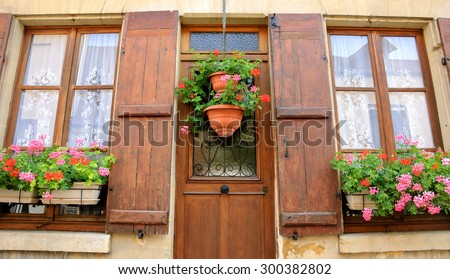 Old house with wooden shutters and door decorated with geranium flower pots. Ile-de-France, France.  - stock photo