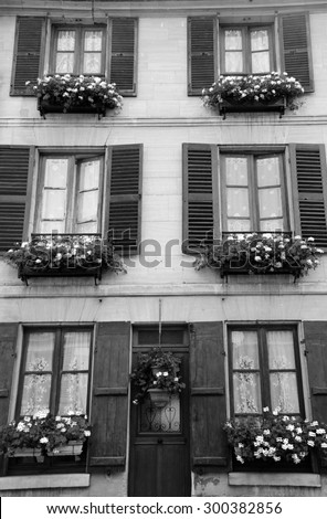 Old house with wooden shutters and door decorated with geranium flower pots. Ile-de-France, France. Retro aged photo. Black and white. - stock photo