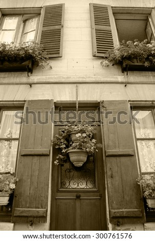 Old house with wooden shutters and door decorated with geranium flower pots. Ile-de-France, France. Retro aged photo. Sepia. - stock photo