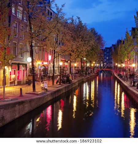 Old houses along canal in the Red Light District of Amsterdam in North Holland, the Netherlands. - stock photo