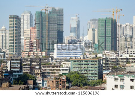 Old houses and new high-rise buildings under construction - stock photo