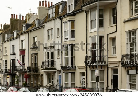 old houses at Brighton,  foreshortening of a row of old houses on an uphill street in touristic sea town,  Brighton, East Sussex  - stock photo