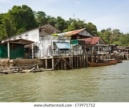 Old houses on the river bank. Thailand