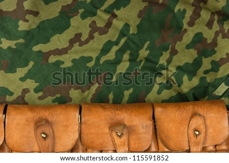 Old hunting cartridges and bandoleer on camouflage background - stock photo
