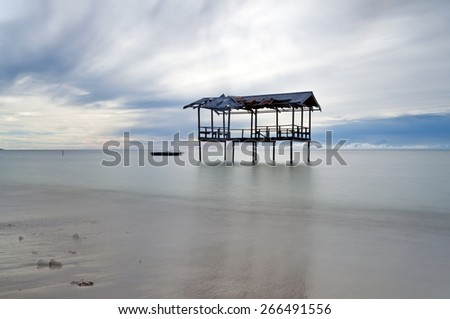 old hut with effect long exposure at kuala penyu beach, borneo sabah, malaysia Image has grain or blurry or noise and soft focus when view at full resolution.  (Shallow DOF, slight motion blur) - stock photo