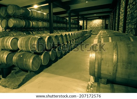 Old image of many wooden barrels in wine cellar - stock photo