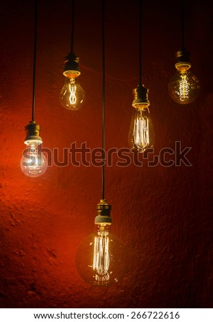 old incandescent lamps lighting together on a wall. Electrical incandescent bulb was a Thomas Alva Edison invention - stock photo