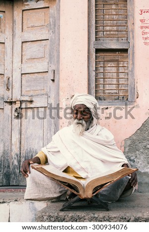 Old indian sadhu (saint) sitting and reading sacred texts near the temple.