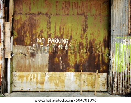 old industrial garage door, background wallpaper. No parking written in english and chinese