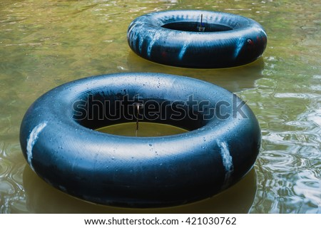 Old inner tubes floating on a river, selective focus - stock photo