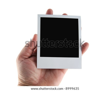 Old instant photo film blank being held in a hand - stock photo