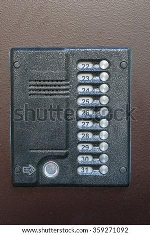 Old intercom (doorphone) in brown door - stock photo