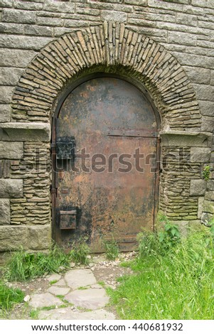 Old iron door in stone wall