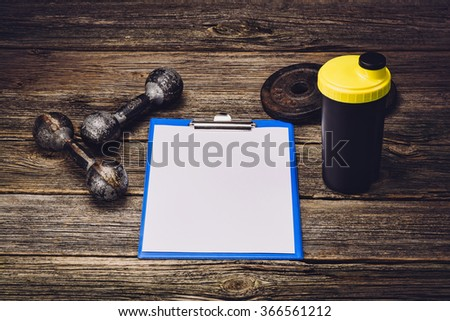 Old iron dumbbells or exercise weights with extra plates on an old wooden deck, floor or table. Image taken from above, top view. A lot of copy space around product. Horizontal photograph, - stock photo