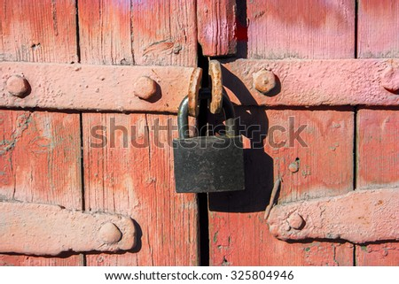 Old iron lock on weathered door painted in red color in Astrakhan, Russia - stock photo