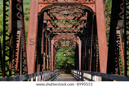 Old, iron railroad bridge converted for foot traffic on a rails to trails path.