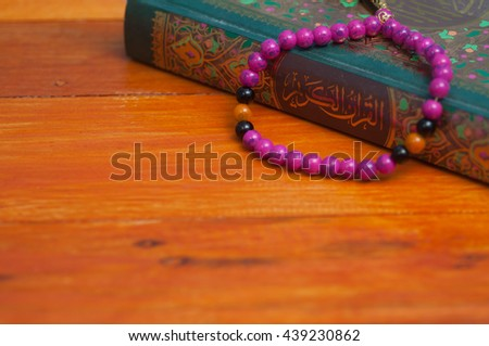 Old Islamic Book Holy Quran and rosary on wooden background - stock photo