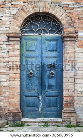 Old Italian architecture details. Blue wooden door with arch in old brick wall, background photo texture - stock photo