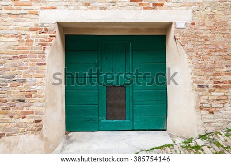 Old Italian architecture details. Green wooden gate in old brick wall, background photo texture - stock photo