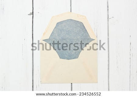Old ivory paper envelope closed on a white wooden background.  - stock photo