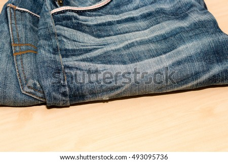old jean or old denim on wooden desk,pattern background from blue jean or blue denim