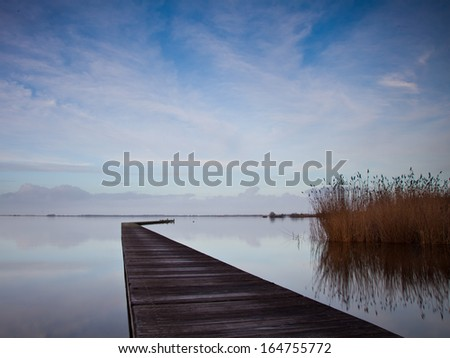 Old Jetty on a Cold Day at a Dutch Lake with Reed and Blue Sky - stock photo