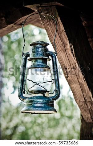 Old kerosene lamp hanging outdoors - stock photo