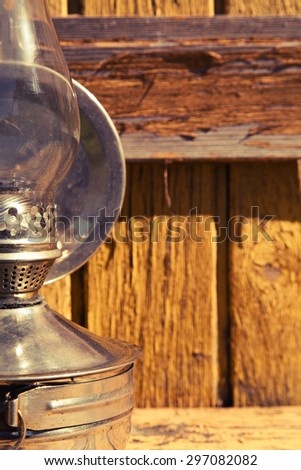 old kerosene lamp stands on wooden surface, outdoors - stock photo