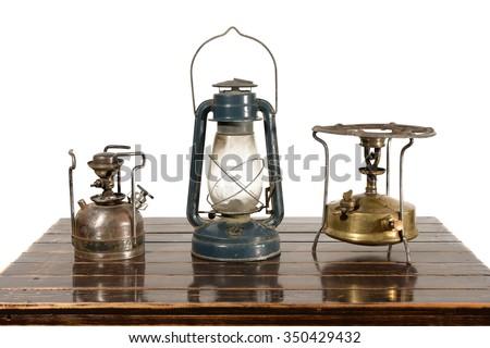 Old kerosene lantern, kerosene stove burner and gasoline. The equipment has withdrawn from use. - stock photo