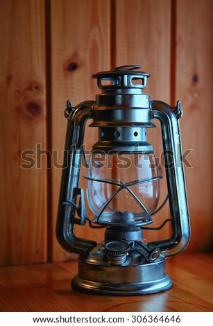 Old kerosene lantern on background wood - stock photo