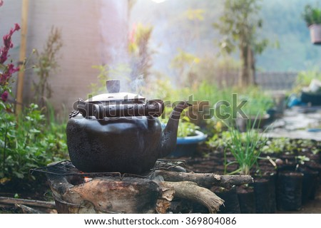Old kettle for boiling water on stove In kitchen the countryside. - stock photo