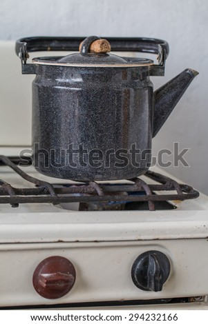 Old kettle on a gas stove flame burn not boiling - stock photo