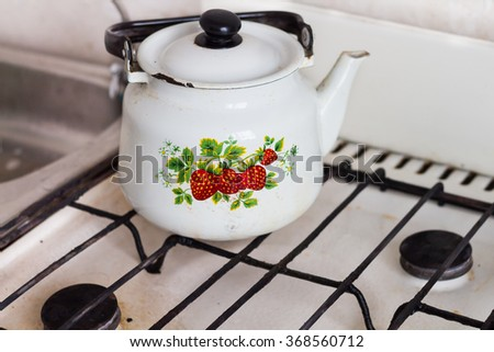 Old kettle on the stove stands - stock photo