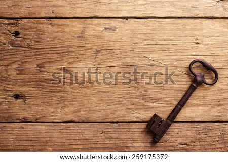 Old key on a wooden background - stock photo
