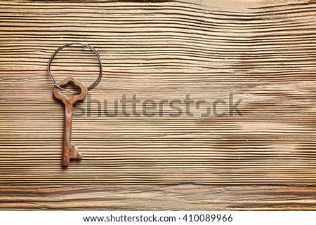 Old key on rustic wooden background - stock photo