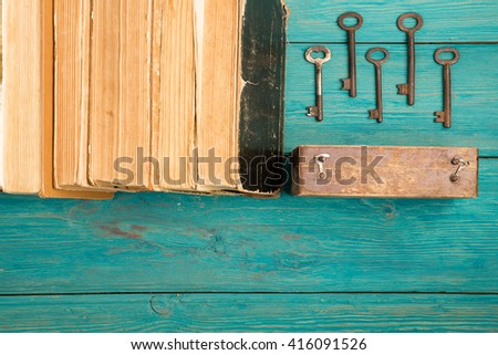 Old keys and stack of antique books on blue wooden background - stock photo