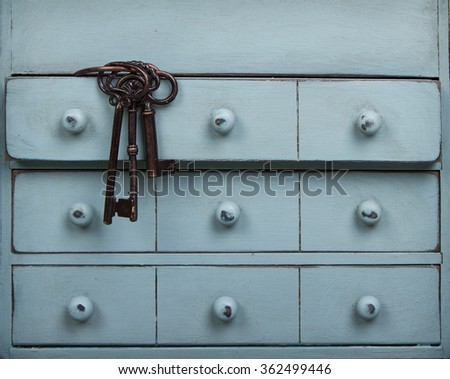 Old keys inside a drawer in a dresser or chest - stock photo