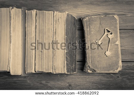 Old keys on a old book and stack of antique books on wooden background. Monochrome - stock photo