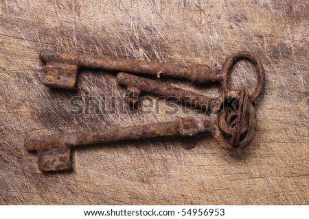 Old keys on worn wooden table, close up. - stock photo