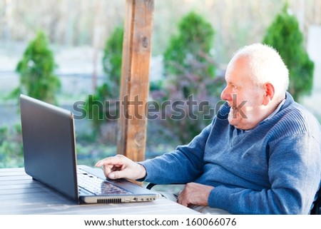 Old kind grandfather trying to use alone the internet. - stock photo