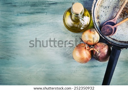 Old kitchen pan wooden spoon three onions carafe with olive oil on wooden table. Some of the equipment of the old kitchen in retro style  - stock photo