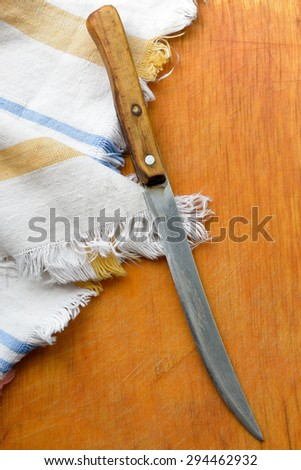 old kitchen towel and old knife on wooden background - stock photo